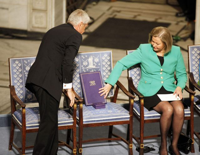 Nobel Commitee chairman Thorbjorn Jagland, left, and committee member Kaci Kullman Five place the Nobel Peace Prize medal and diploma on an empty chair representing Nobel Peace Prize laureate Liu Xiaobo
