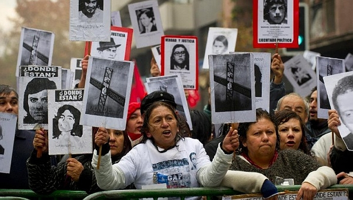 Demonstrators holding posters with the portraits of missing or killed relatives protest in Santiago