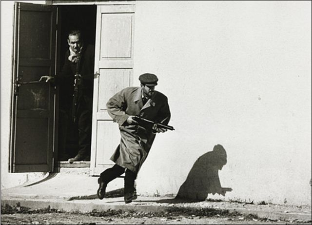 Turkish Cypriot sprinting from a cinema door under fire, Limassol, Cyprus, 1964