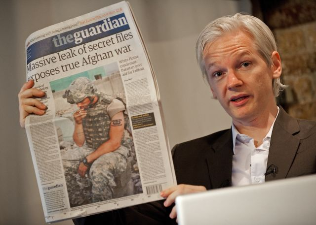 Julian Assange, leader of WikiLeaks, holds up a copy of the Guardian with a front page article that used leaked Pentagon data. during a press conference in London on July 26, 2010.  The