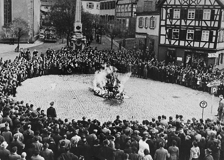 German civilians watch as the furnishings of the Mosbach synagogue are burned in the town square