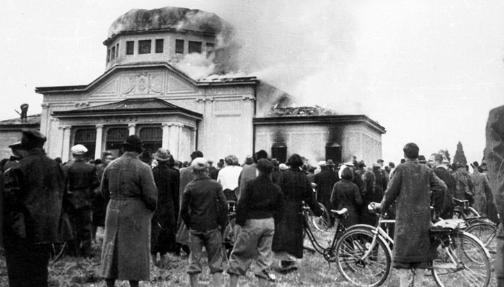 Residents in Graz, Austria, watch as the Jewish cemetery's ceremonial hall burns
