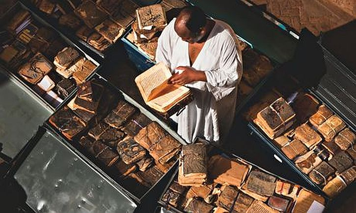 Abdel Kader Haïdara with ancient manuscripts from Timbuktu packed into metal trunks
