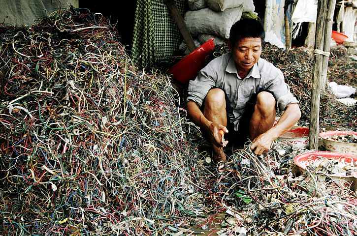 A worker rummages through electronic waste for the purpose of salvaging metals and other materials