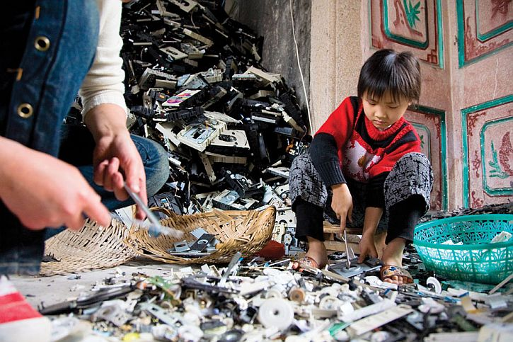 A young girl disassembles computer CD drives. Early exposure to heavy metals produces a disproportionate rate of infant mortality and unusually low IQs among Guiyu's children.