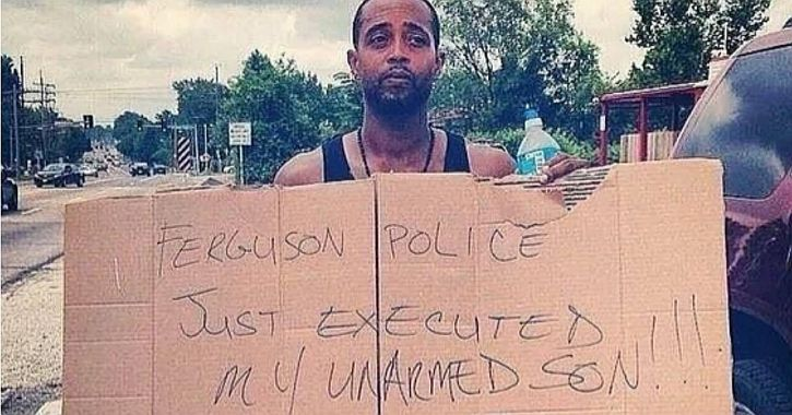 Michael Brown's father holds a sign in protest of his son's killing