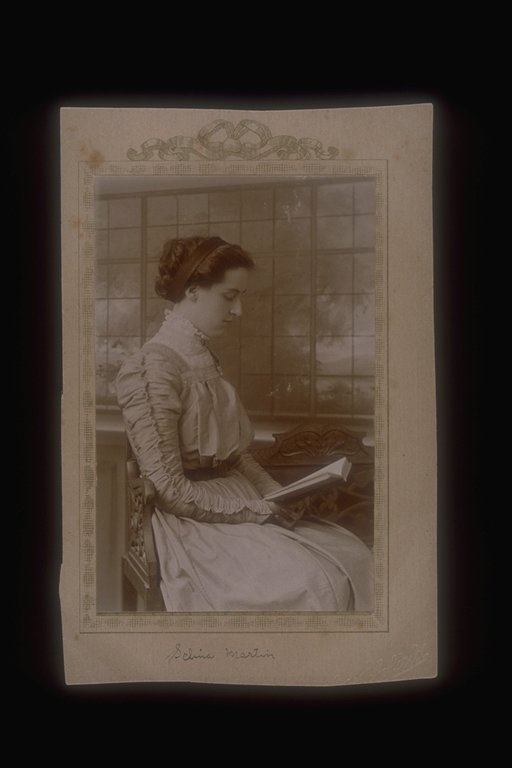 Photograph of Selina Martin reading a book. Handwritten on the back is 'From Selina Martin'. photograph taken by Ada Schofield, a Brighton photographer and suffragette.