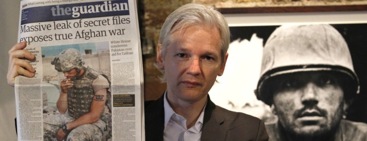 Wikileaks founder Julian Assange holds up a copy of the Guardian newspaper during a press conference