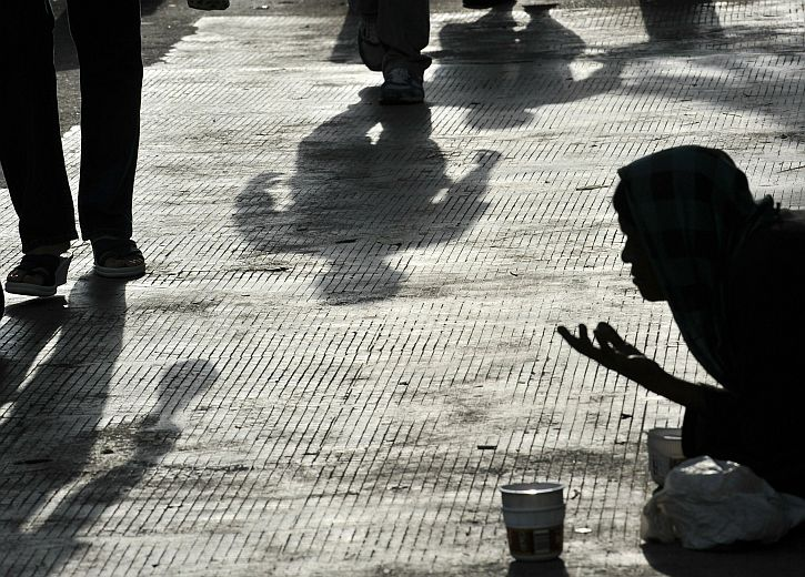 A beggar asks for alms along a pedestria