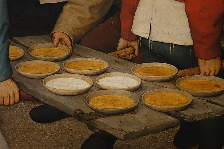 The Peasant Wedding, detail: plates of porridge on an old door