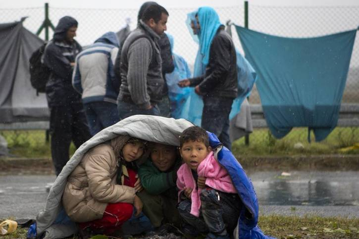 Children take shelter from the rain in Sredisce ob Dravi, a border crossing between Croatia and Slovenia
