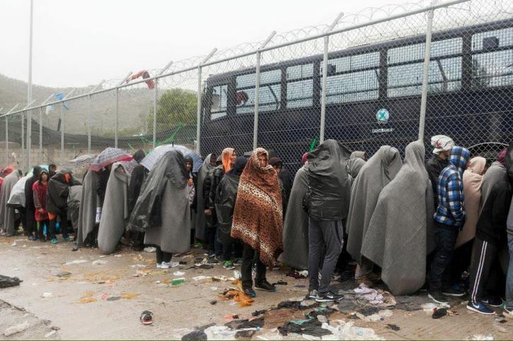 Refugees queue in the rain in Calais