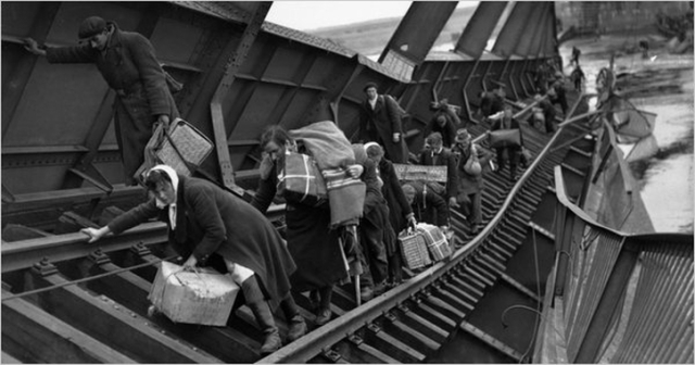 Refugees from Eastern Europe cross a war-damaged railway bridge over the Elbe River. May 1945