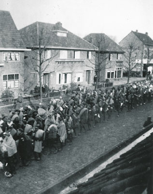 Jews are marched through the streets of Vught after the arrival of one of the first prisoner transports in January 1943