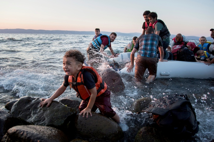 A group of Syrians arrives on Lesvos after sailing on an inflatable raft from Turkey