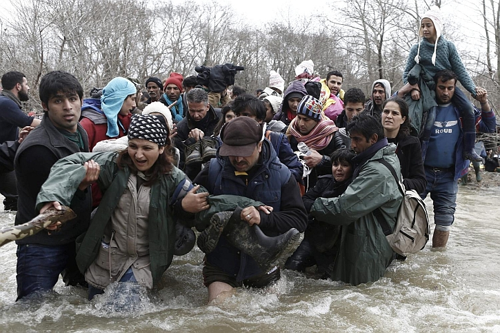 Refugees criossing a swollen river on the Greek-Macedonian border 14 March 2016