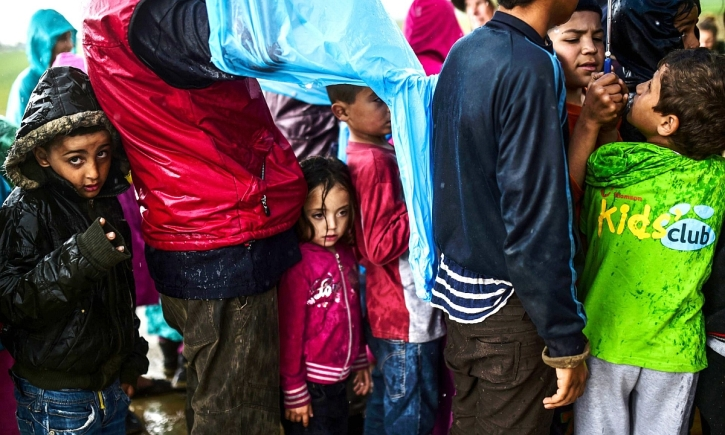 Child refugees queuing for food at the makeshift camp at Idomeni, northern Greece