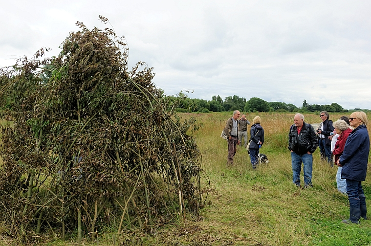 The group inspects a likely reconstruction of one of the Mesolithic huts at Lunt Meadows