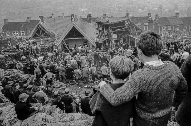 Two surviving children watch the miners digging to find children still buried in the slag that swept over their school: David Hurn's iconic photograph