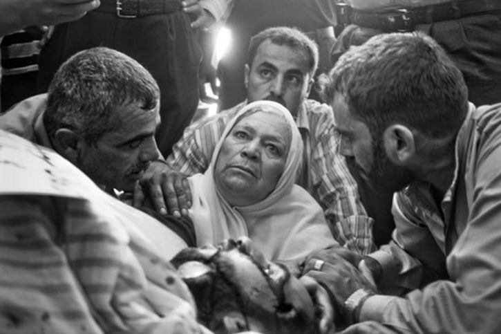 Aleppo. July 23, 2012: Fatma Al-Krama cradles the body of her dead son, 25-year-old Habib Al-Krama, tortured and killed by pro-Assad militias. (Photo by Moises Saman of Magnum)
