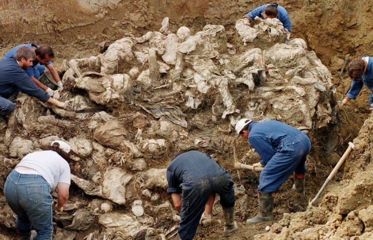 1996: International War Crimes Tribunal investigators clear away soil and debris from dozens of Srebrenica victims buried in a mass grave