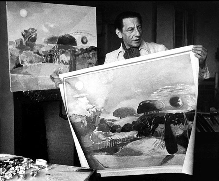 Paul Nash in his studio with two versions of 'Landscape of the Vernal Equinox'.