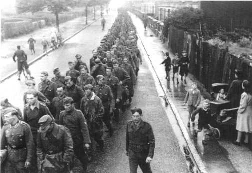 German prisoners are marched under guard, through an English street on their way into captivity. Scenes like this were common in England in the months following D-Day.